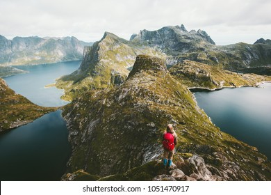 Woman hiker alone with backpack hiking on mountain ridge Traveling lifestyle adventure concept active vacations in Norway outdoor aerial view