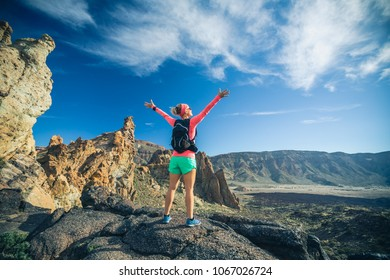 Woman hiker with arms outstretched in mountains reached life goal. Female runner or climber with hands up enjoy inspirational landscape on rocky trail footpath on Tenerife, Canary Islands Spain
