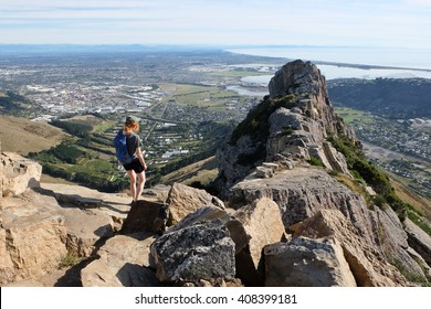 Woman Hiker Ascending Castle Rock.  Port Hills, Christchurch, New Zealand.