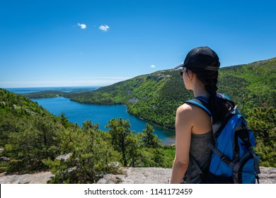 Woman hiker atop a mountain overlooking Jordan Pond in Acadia National Park