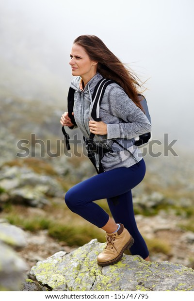 Woman hiker with backpack climbing on the mountain over a misty background