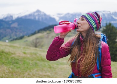 Woman hiker with backpack driking from reusable water plastic bottle outdoors in nature