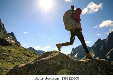 Woman hiker with backpack hiking on high altitude mountain top