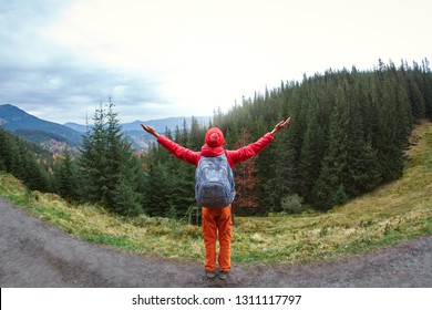 woman hiker with backpack standing with raised hands on the mountain trail against background of mountains, pine woods and cloudy sky. back view