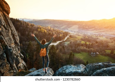 woman hiker with backpack stands on edge of cliff against background of sunrise. Woman is meditation and greeting a sun