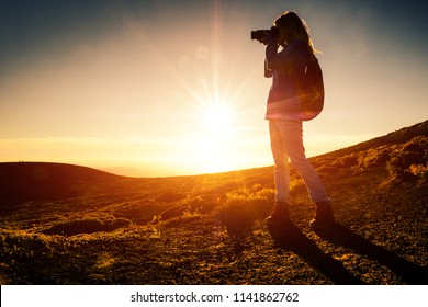 Woman hiker with backpack takes picture of the landscape in mountains during golden hour