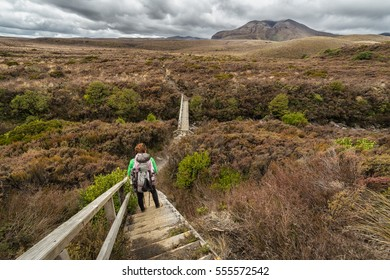 Woman hiker with backpack tramping on Tongariro national park in New Zealand