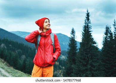 woman hiker with backpack, wearing in red jacket and orange pants, standing on the mountains, cloudy sky and woods background and sightseeing, Western Ukraine.