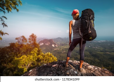 Woman hiker with big backpack stands on the rock and enjoys the valley view