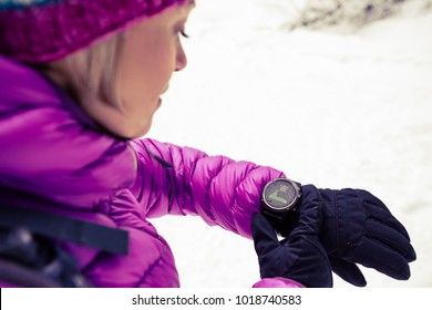Woman hiker checking the elevation on sports watch, smartwatch with altimeter app in winter woods and mountains. Female trekker in white snowy forest trekking with electronics equipment technology.