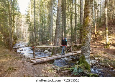 Woman hiker crossing a footbridge in forest across a pure mountain river, with a blaze drawn for direction, sun shining. Active lifestyle, pristine nature concept.