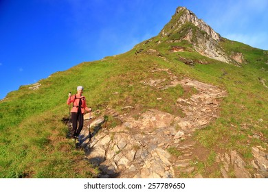 Woman hiker descending on narrow trail along sunny mountain in the morning