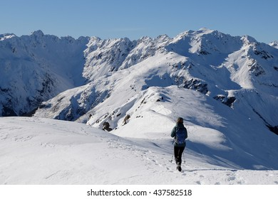 A Woman Hiker Descends a High and Snowy Peak with Mountain Views Beyond.  Mt Bealey, Arthurs Pass, Southern Alps, Canterbury, New Zealand