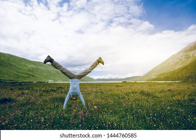 Woman hiker doing a handstand on high altitude mountain meadow