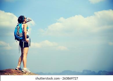 woman hiker drink water at mountain peak cliff