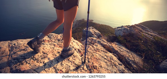 woman hiker enjoy the view at sunrise seaside mountain peak cliff edge
