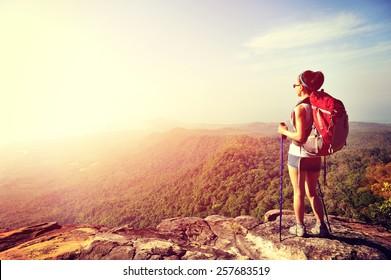 woman hiker enjoy the view at sunset mountain peak cliff