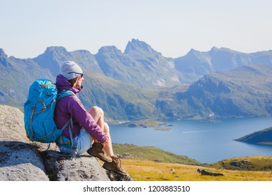 Woman hiker enjoying at the top of the mountain and looking at incredible views of a Norwegian fjord, Lofotens. Travel, adventure, healthy lifestyle concept