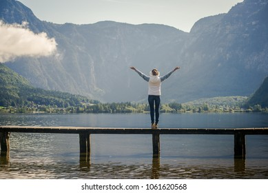 Woman hiker enjoys good weather. Physical activity in the journey. Young tourist woman on the bridge and enjoy the relaxation and freedom. Beautiful view of the mountain nature. Girl doing yoga