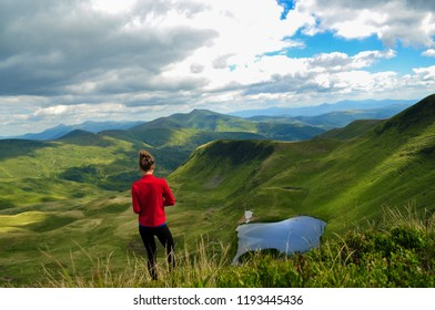 Woman hiker hiking looking at scenic view of mountain lake landscape . Adventure travel outdoors person standing relaxing near lake during nature hike in summer season. Carpathian Mountain- Image