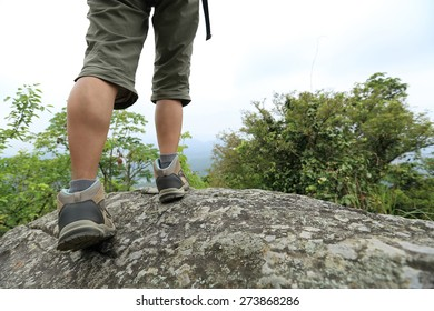 woman hiker  legs at mountain peak cliff