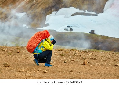 woman hiker photographer taking photo on the rhyolite mountains background in Iceland