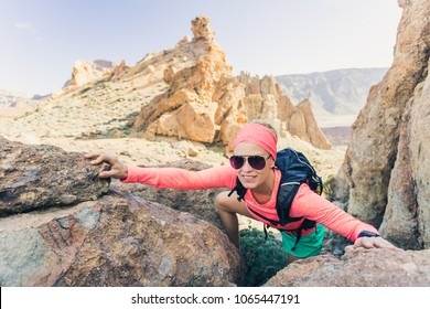 Woman hiker reached mountain top. Runner or climber walking and looking at inspirational landscape on rocky trail on Tenerife, Canary Islands Spain. Fitness and motivation activity concept.