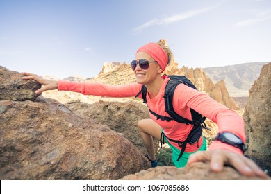 Woman hiker reached mountain top. Inspiration and motivation for weekend adventures. Female runner or climber looking at inspirational landscape on rocky trail on Tenerife, Canary Islands Spain.