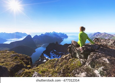 Woman hiker relaxing at the top of the mountain and looking at incredible views of a  Norwegian fjord on Senja Island, northern Norway