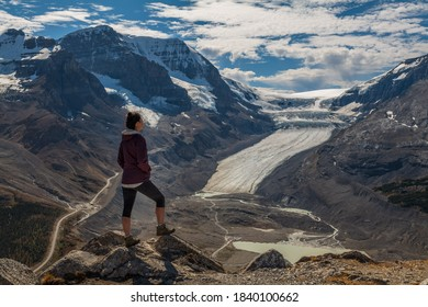 Woman hiker standing on Wilcox peak looking out over the Columbia icefields and the Athabasca Glacier, in Jasper, Alberta, Canada