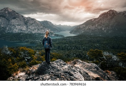 Woman hiker stands and enjoys valley view from viewpoint. Hiker reached top of the mountain and watching sunset. Patagonia, Argentina