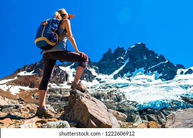 Woman hiker stands on the rocks and enjoys glacier view of the Cerro Castillo Mountain, Patagonia, Chile.