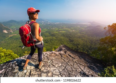 Woman hiker stands on top of the mountain and smiles and looks into camera