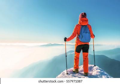 Woman hiker successful on mountain peak summit in winter mountai