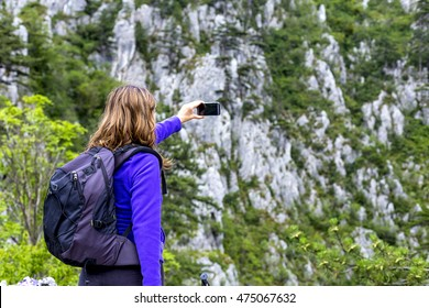 Woman hiker taking photo with her smart phone at the mountain peak