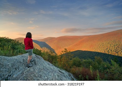 a woman hiker taking in the view at the top of a mountain at sunset