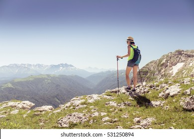 Woman hiker with trekking poles and backpack on a top of a mountain