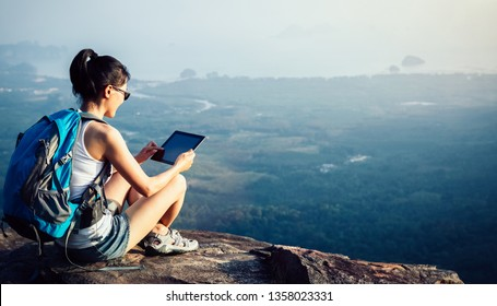 woman hiker use digital tablet taking photo at mountain peak cliff