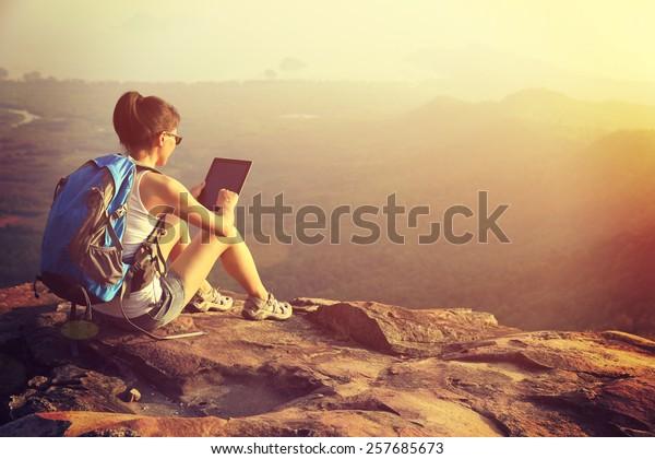 woman hiker use digital tablet at mountain peak cliff