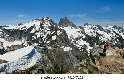 A Woman Hiker Views Thorton Peak and Mt. Fury from the Summit of Trappers Peak.  North Cascades National Park, Washington