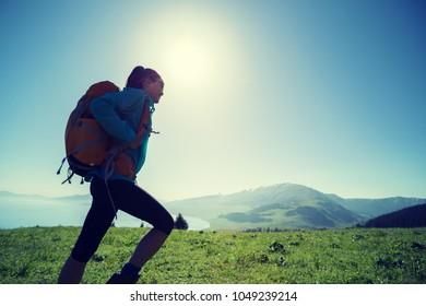 woman hiker walking on beautiful green mountain hill top