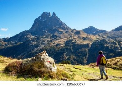 A woman hiker walking in the Pyrenees mountains near the Pic Ossau