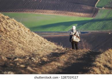 Woman hiker walks on the hill