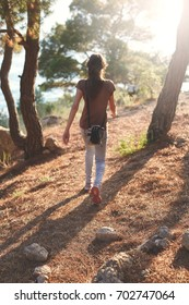 Woman hiker walks on the trail outside in forest with backpack and looking at the sea