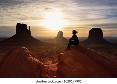 Woman hiker watching beautiful scenery of sunrise in Monument valley, Utah, USA