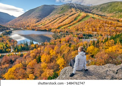 Woman hiking at Artist's Bluff in autumn. View of Echo Lake. Fall colours in Franconia Notch State Park. White Mountain National Forest, New Hampshire, USA