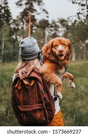 A woman hiking with a dog, Nova Scotia Duck Tolling Retriever (Toller) in the woods.