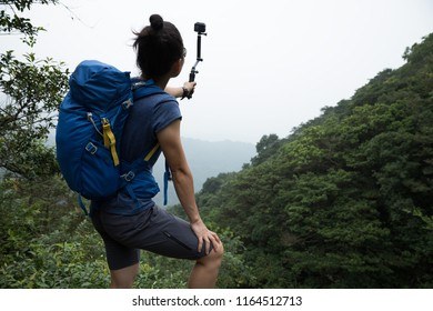 Woman Hiking In Forest Taking A Selfie with action camera