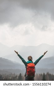 Woman Hiking in High Mountains on Stormy Moody Weather. Female tourist with backpack on a trail with clouds and fog covered mountains background, spring, autumn or winter. Extreme Adventures.
