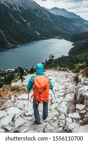 Woman Hiking in High Mountains on Stormy Moody Weather. Female tourist with backpack on a trail with blue mountain lake in background, spring, autumn or winter. Extreme Adventures.
